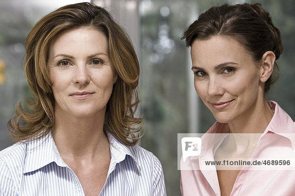 Zwei lächelnde Frauen Seite an Seite