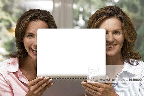 Zwei fröhliche Frauen halten Laptop