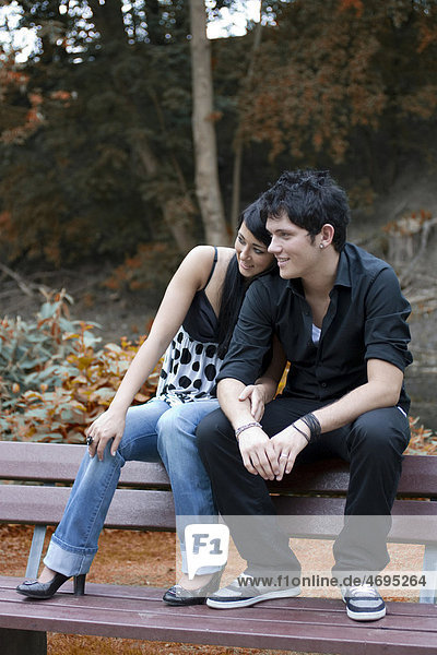 Paar  Südländer  sitzen auf der Lehne einer Parkbank