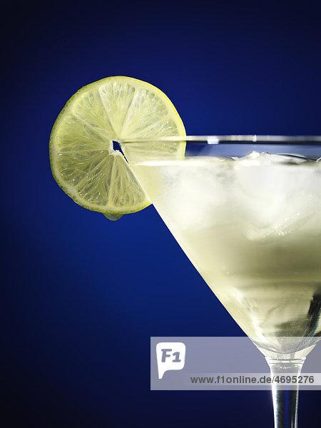 Eisgekühlter Cocktail in einem Martini-Glas  mit Limettenscheibe garniert