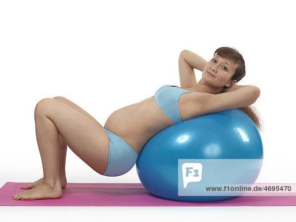 Schwangere junge Frau beim Pilates Workout mit einem Fitnessball