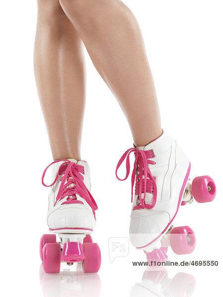 Nahaufnahme der Beine einer jungen Frau mit rosa-weißen Rollschuhen