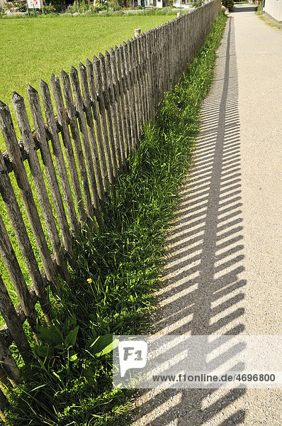 Wooden fence separating a path from a lawn  Fraueninsel island on Lake Chiemsee  Chiemgau  Upper Bavaria  Bavaria  Germany  Europe