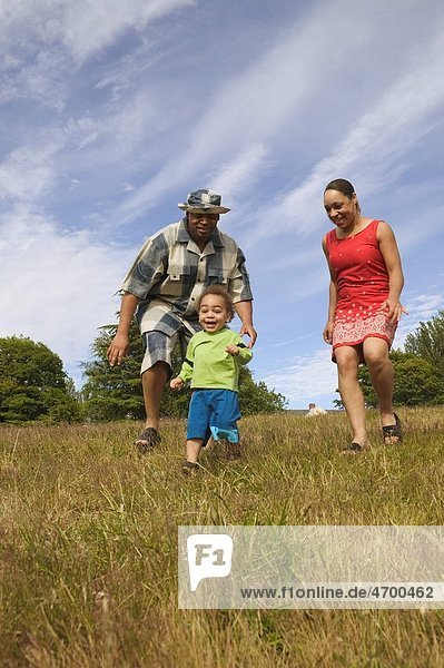 A couple chasing their small son in a grassy field.