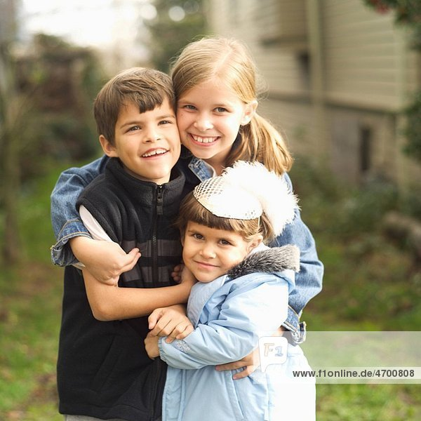 Portrait of three young siblings outdoors.