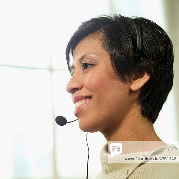 Woman wearing a telephone headset.