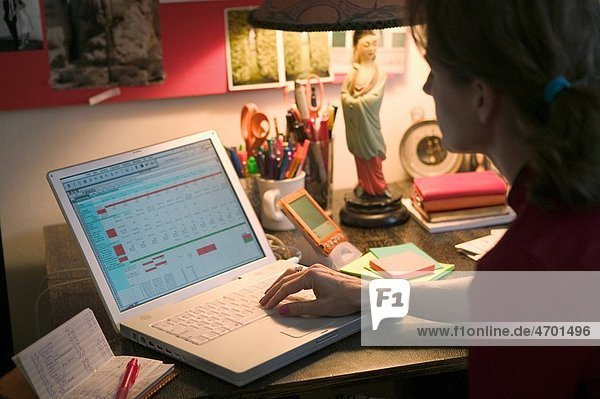 Woman working on her budget at a home office desk.