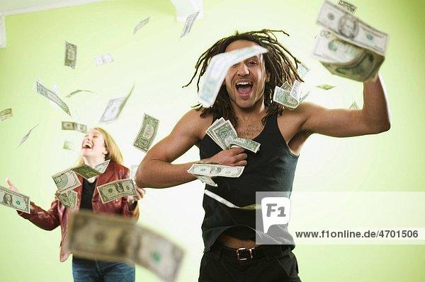 Man and woman catching falling money.