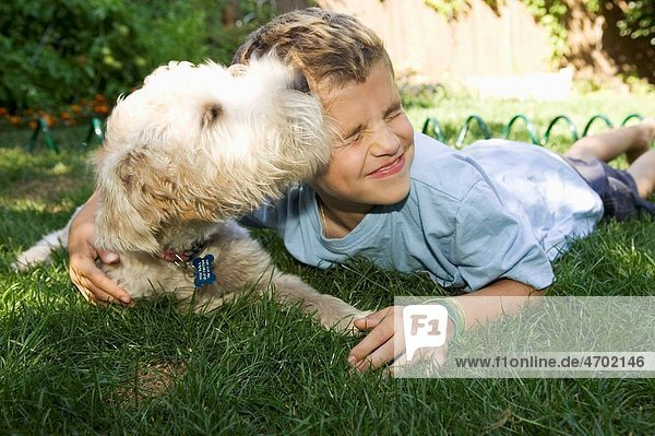 Boy and dog lying down together outdoors