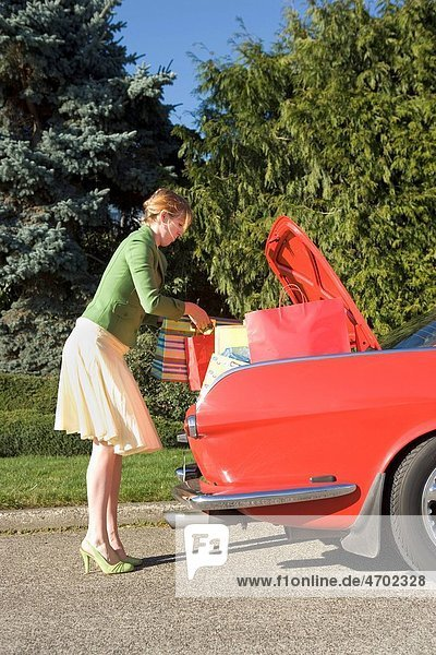 Woman removing shopping bags from car