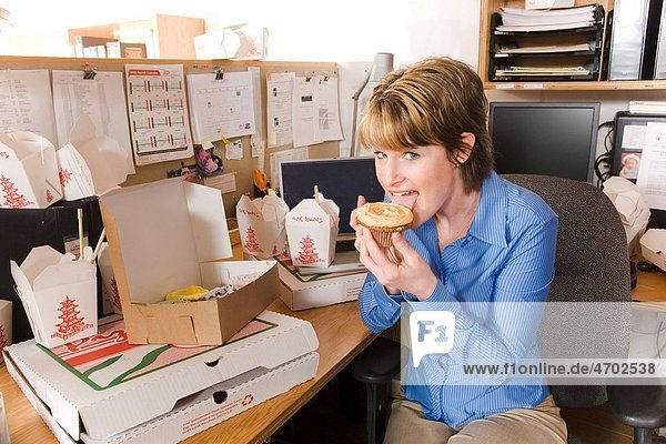 Office worker eating at her desk