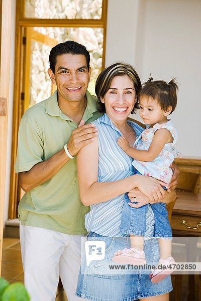 Parents posing with toddler in home