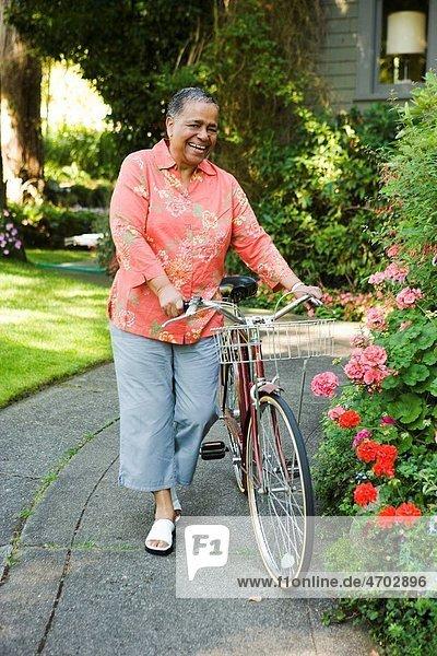 Smiling woman walking her bicycle