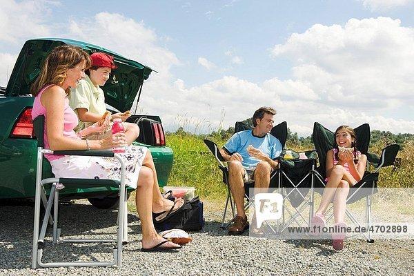 Family enjoying picnic lunch outside car
