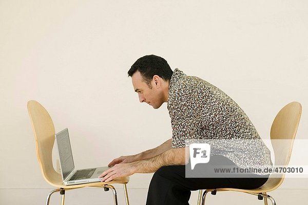 Man using laptop in bare room