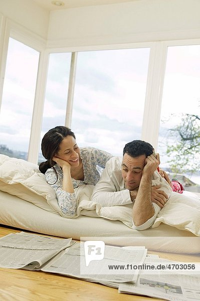 Couple on bed looking at newspaper