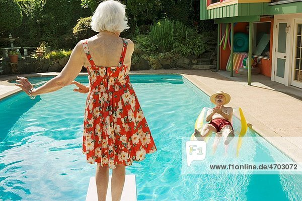 Senior couple having poolside fun