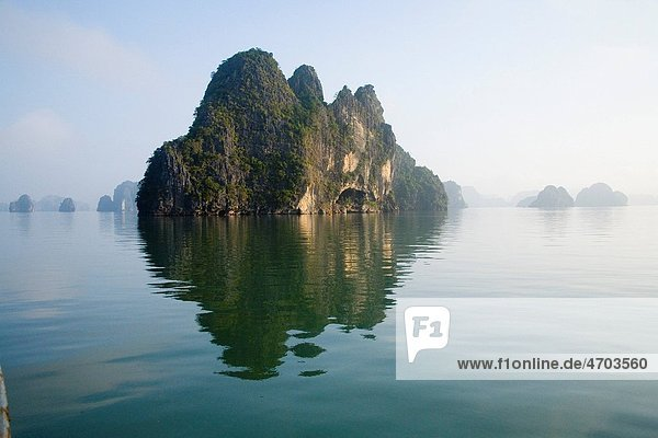 Rocky islands with still water in misty morning