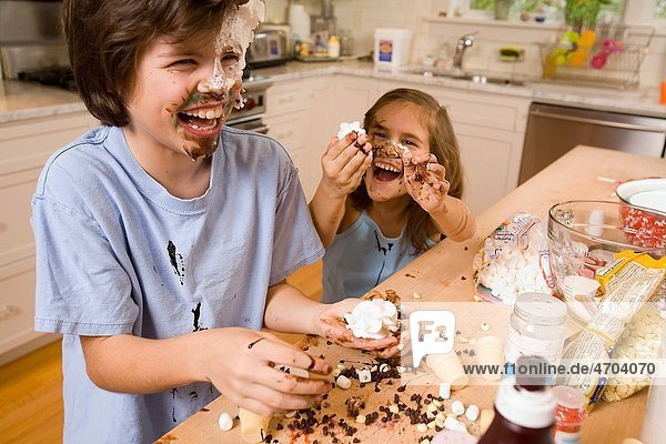Boy and girl making mess in kitchen