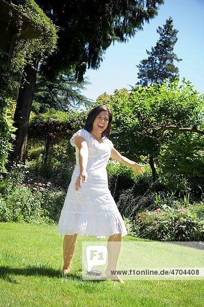 Woman standing in sprinkler in her backyard