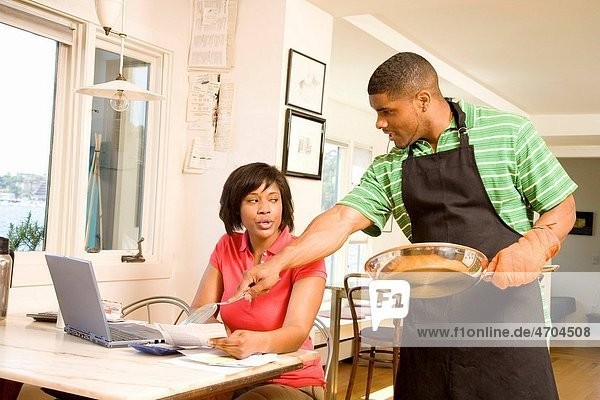 Man cleaning a pan as wife writes checks