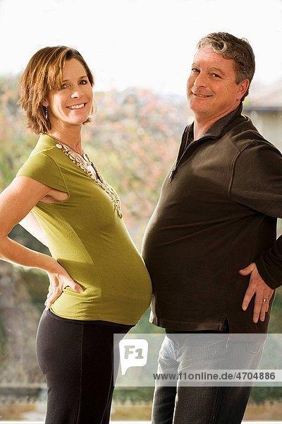 Portrait of pregnant couple touching bellies