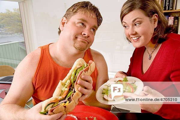 Woman offering her husband a salad instead of sandwich