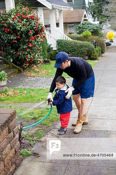 Father and son watering plants