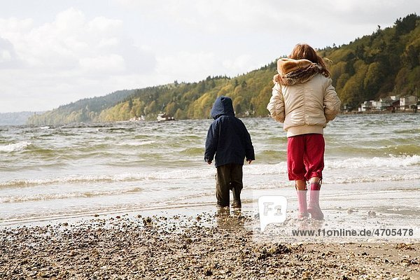 Young boy and girl walking on beach
