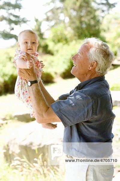 Senior man holding baby