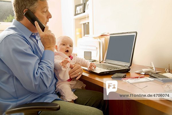 Businessman working with baby on lap