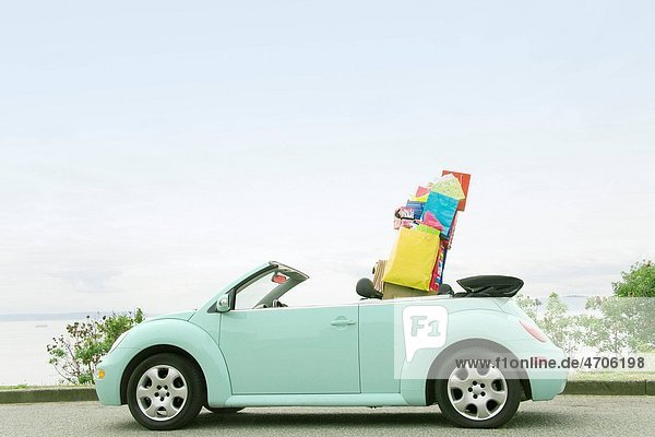 Convertible car with shopping bags in backseat