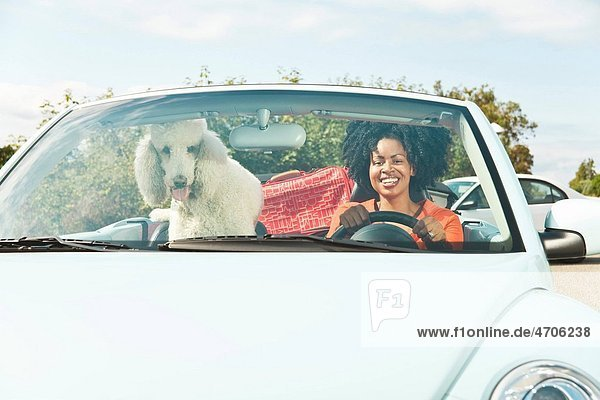 African woman and dog in convertible car