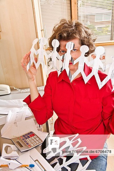 Woman holding row of paper dolls in home office