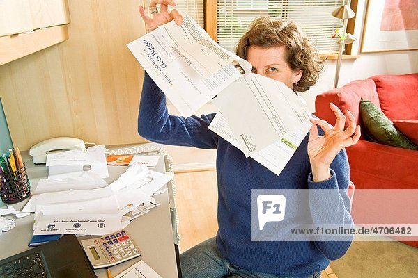 Woman holding bills in home office