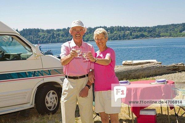 Couple toasting glasses of wine at a beach  Washington State  USA
