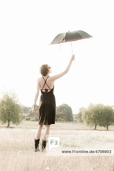 Woman holding an umbrella in a field
