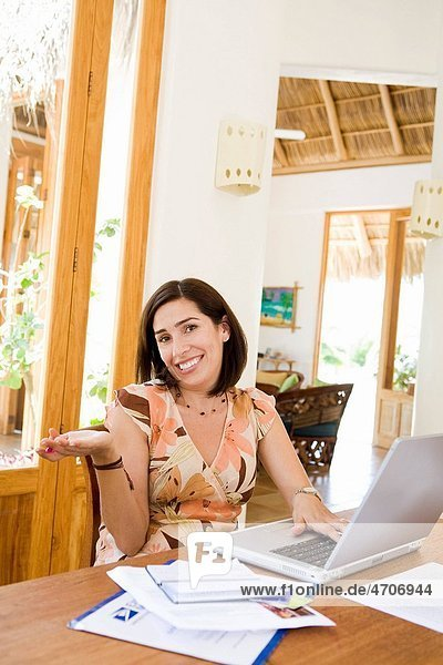 Woman sitting in front of a laptop and shrugging