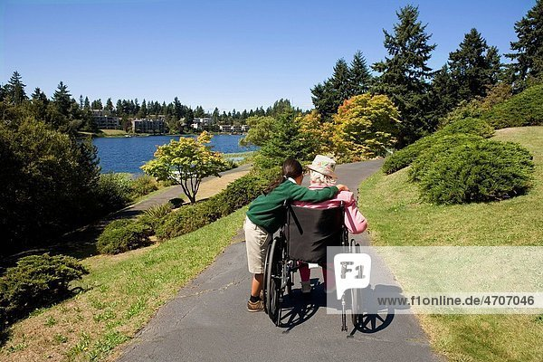 Girl assisting a disabled woman in a wheelchair