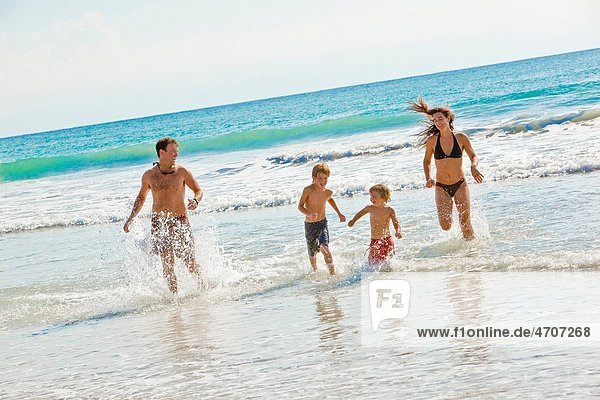 family running on beach in mexico