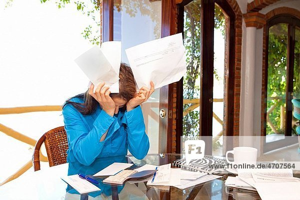 woman paying bills at dining room table
