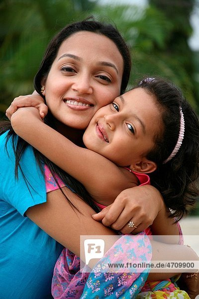South Asian Indian mother and daughter hugging each other and smiling MR3687H687E