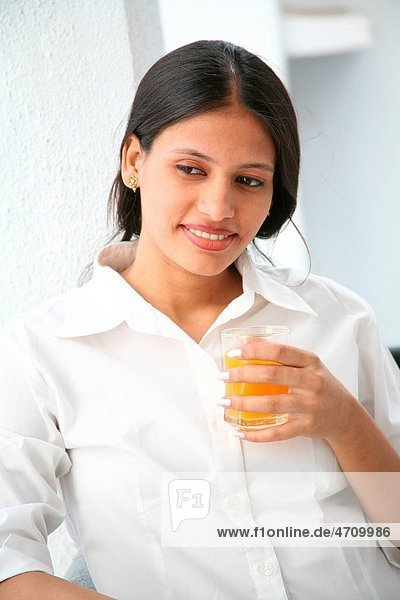 South Asian Indian young pregnant married lady holding glass of fruit juice MR687 Q