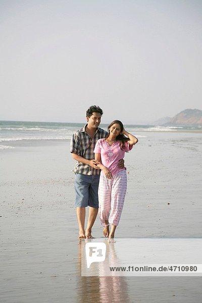 South Asian Indian young man and woman holding hands walking together on seashore  Shiroda  Dist Sindhudurga  Maharashtra  India MR703D  703E