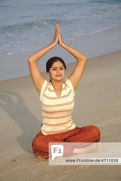 South Asian Indian young lady doing yoga sitting in padmasan posture on seashore   Shiroda   Dist Sindhudurga   Maharashtra   India MR703E