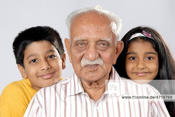 South Asian Indian grandfather with grandchildren looking at camera MR152