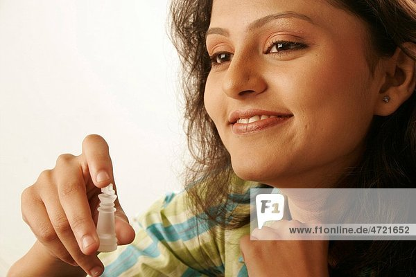 South Asian Indian teenage girl smiling and holding King key of chess in fingers MR686M