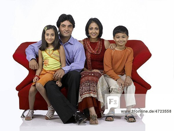 South Asian Indian family with father mother son and daughter sitting on sofa looking at camera MR 698   699   700   701