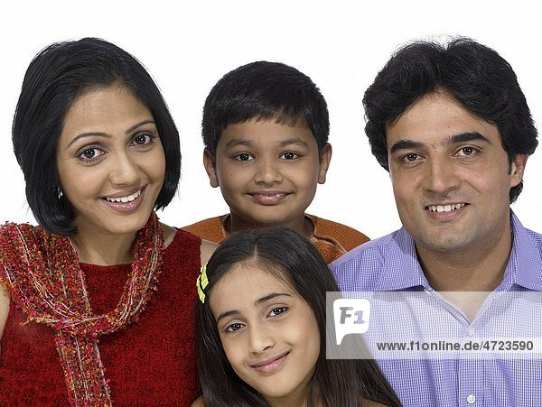 South Asian Indian family with father mother son and daughter smiling and looking at camera MR 698   699   700   701