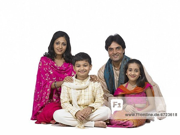 South Asian Indian family with father mother son and daughter sitting smiling and looking at camera MR 698   699   700   701